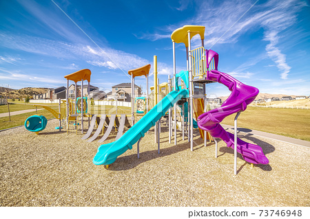 Colorful blue and purple slides in kids playground 73746948