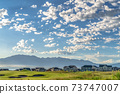 Lovely view of a golf course and residential area near a lake on a sunny day 73747007