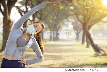 Young asian woman wear mask and doing exercises 73747822