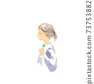 A woman clasping a four-leaf clover 73753882