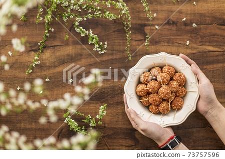 雙手拿盤中熟食牙籤肉丸配花朵 73757596