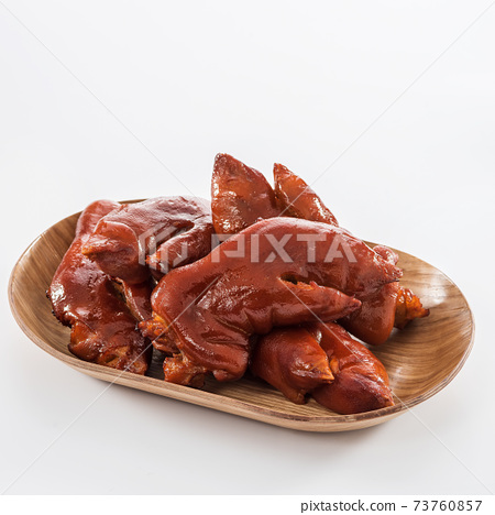 Braised pig's trotter in wooden plate on white background 73760857