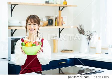 戴著眼鏡在廚房裡拿著一個蔬菜碗的圍裙的女人 73764369