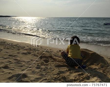 황혼의 해변에서 모래 장난을하는 소년 73767471