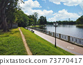 Pedestrian walkway around city pond embankment 73770417