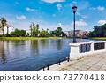 Street lantern on embankment of city pond at day 73770418