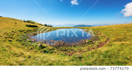 pond on the mountain meadow. beautiful summer landscape in morning light. grass on the hills. ridge in the distance 73774270