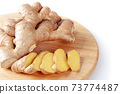 Fresh sliced ginger root on a round cutting board. 73774487