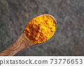 Turmeric powder on a wooden spoon above a gray background 73776653
