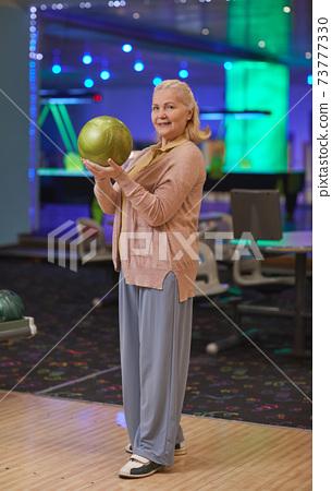 Smiling Mature Woman Playing Bowling 73777330