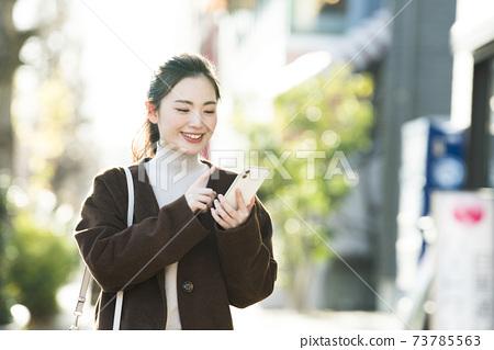 尋找在她的智能手機上一個年輕女子目的地 73785563
