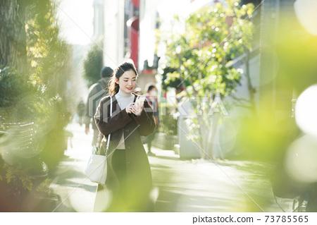 尋找在她的智能手機上一個年輕女子目的地 73785565