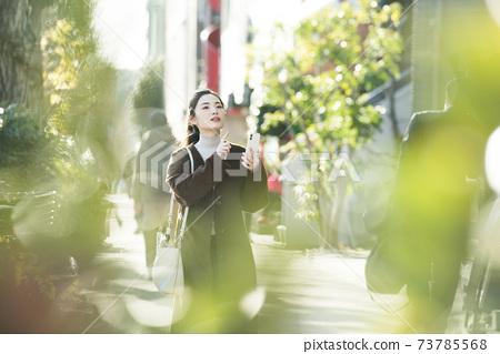 尋找在她的智能手機上一個年輕女子目的地 73785568