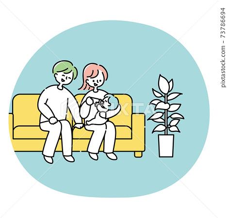一對夫婦在沙發上給他們的嬰兒牛奶 73786694