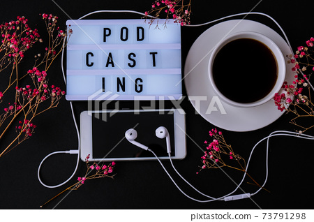 Podcasting lettering. Headphones mobile phone. Dry pink flowers decoration. Workplace. Black coffee 73791298
