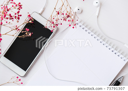 Open blank notebook with headphones mobile phone. Black screen and black pen. Copy space foe text. Top view. Dry pink flowers decoration. Workplace. 73791307