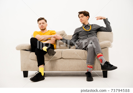 Two cute guys make a bet hand in hand sitting on a white sofa. Group of friends are sitting on a soft couch and communicates isolated on white background 73794588