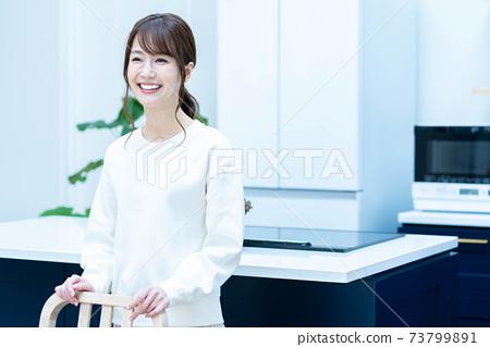 站立在廚房裡的一名微笑的婦女 73799891