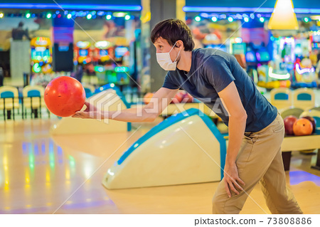 Man playing bowling with medical masks during COVID-19 coronavirus in bowling club 73808886
