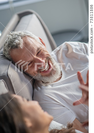 Smiling grey-haired man looking at his spouse 73811886