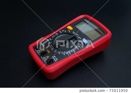 Red digital multimeter with on black table 73811950