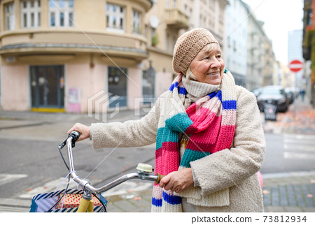 Senior woman with bicycle crossing road outdoors in city. 73812934