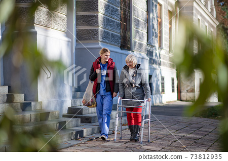 Senior woman with walking frame and caregiver outdoors in town, shopping and coronavirus concept. 73812935