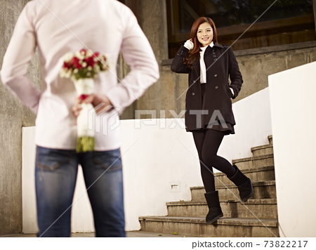 asian young man waiting by the steps with flowers behind back for his girlfriend 73822217