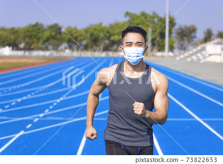 Man in medical mask and running  on the track 73822653