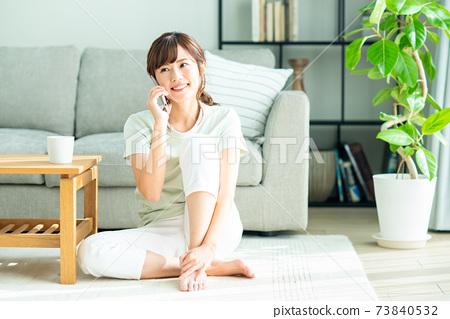 거실에서 전화를하는 젊은 여성 73840532