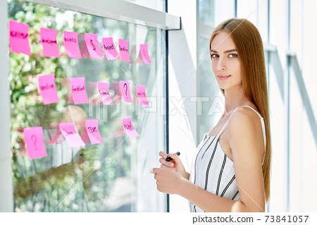 Attractive confident business woman using sticky notes to write and share ideas in creative office 73841057