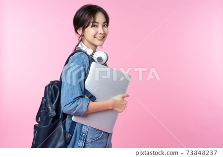 Young happy Asian woman holding laptop 73848237