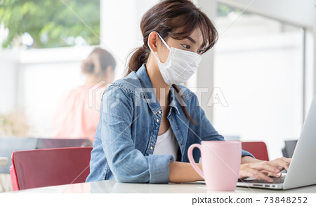 Asian student girl working at a coffee shop with a laptop she wearing hygienic mask 73848252