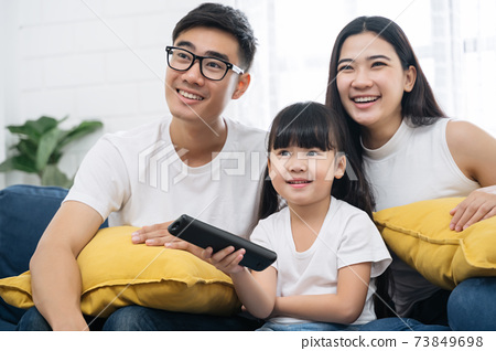 Asian family spending time by watching tv 73849698