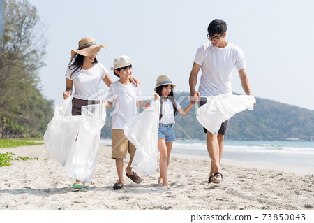 Asian Family volunteer picking up a plastic bottle on a beach with a sea to protect an environment 73850043
