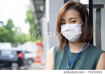 Portrait Asian business woman wearing hygienic mask outside office 73850891