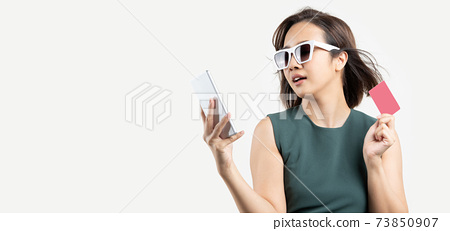 Asian woman with glasses shopping by phone and hold credit card 73850907
