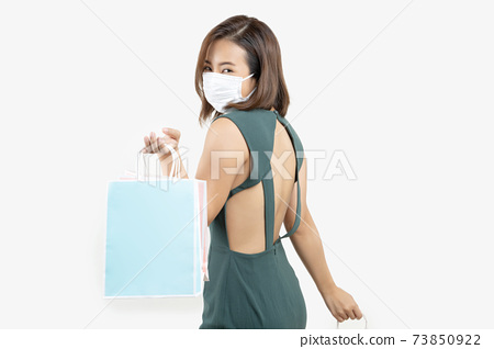 Young Asian woman holding shopping bag wear face mask 73850922