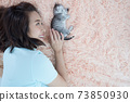 Young Asian woman with kitten cat pet sleep on the bed 73850930