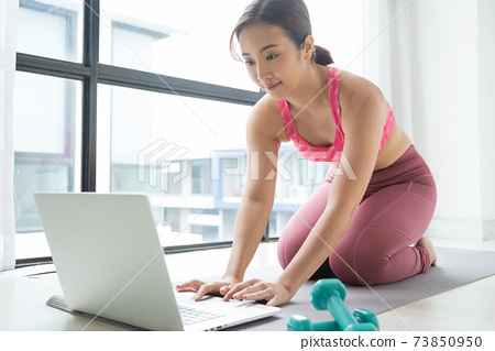 Woman training fitness at home watch online tutorial on laptop 73850950
