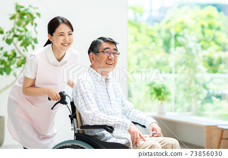 A young woman caring for a senior man in a wheelchair 73856030