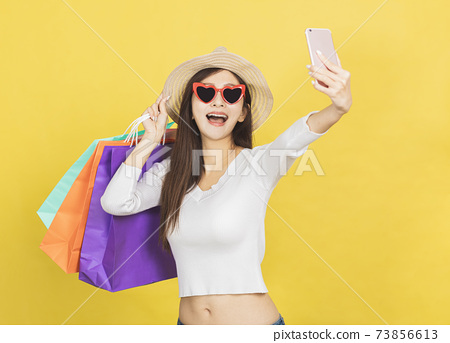 happy young woman holding shopping bags and watching the mobile phone 73856613