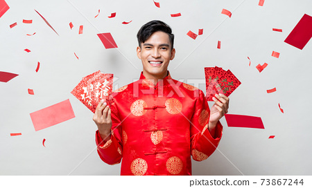 Smiling happy Asian man in oriental costume holding red envelopes or Ang Pao 73867244