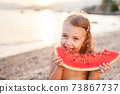 Girl is holding slice of red watermelon on beach at sunset. Summer fun holiday and travel concept Child is happy tourist 73867737