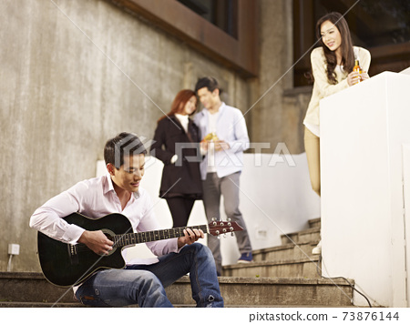 young asian adult friends hanging out playing guitar drinking beer outdoors 73876144