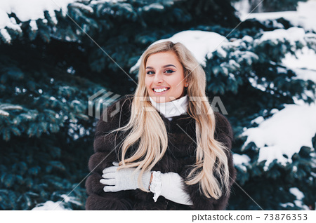 Smiling woman standing in winter snowy forest. Winter holidays concept 73876353