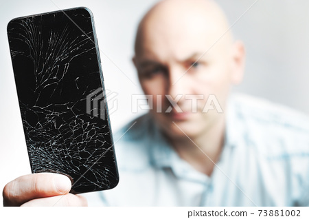 Phone With A broken screen close-up. A white man is holding a black smartphone with a cracked 73881002