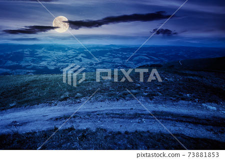 mountain road through grassy meadow at night. wonderful summer adventure in full moon light. clouds on the blue sky 73881853