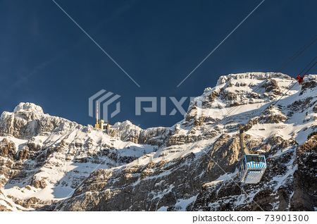 The snow-covered Saentis with summit station and cable car, Switzerland 73901300
