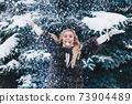 Happy girl in warm clothes playing with snow outdoors in the winter forest 73904489